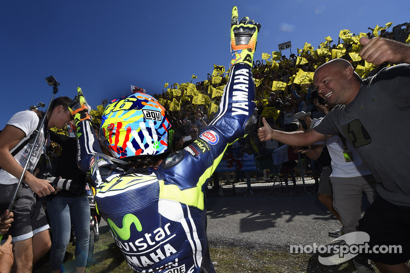Race winner Valentino Rossi celebrates with fans