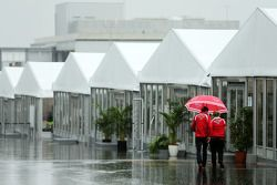 Jules Bianchi, Marussia F1 Team and Tracy Novak, Marussia F1 Team PR & Communications Director in a wet and rainy paddock