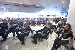 Factory workers listen to Lewis Hamilton and Nico Rosberg