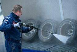 A Volkswagen mechanic cleaning wheels