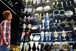 Sebastian Vettel looks at trophies at the Red Bull Racing factory