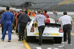 Les membres d'équipe poussent les voitures vers la ligne de qualification