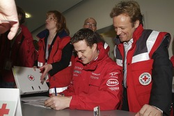 German Red Cross ambassador Uwe H��bner helps Ralf Schumacher logo visitors