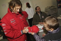 Jarno Trulli logos a Panasonic Toyota Racing cap for a young fan