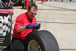 A crew member removes rubber from a Goodyear Eagle