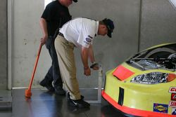 A NASCAR offical inspects the front end of a Busch car