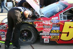 Kyle Busch's crew inspect the damage to his car