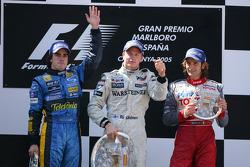 الفائز بالسباق كيمي رايكونن مع فرناندو ألونسو ويارنو تروللي