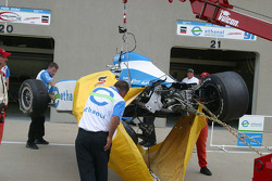 Ron Hemelgarn watches from the garage as team members inspect the damage to Paul Dana's car
