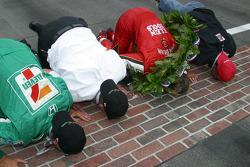 Kim Green, Kevin Savoree, Dan Wheldon and Michael Andretti kiss the bricks in celebration of the victory