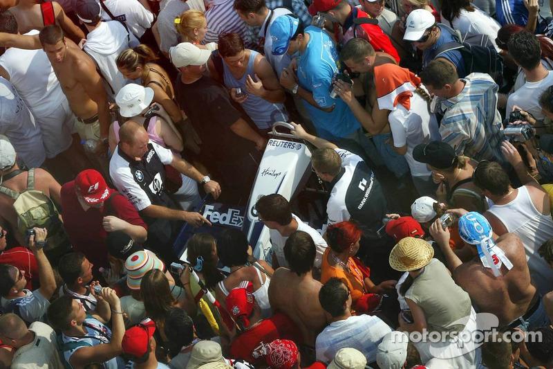 Los miembros del equipo Williams intentan hacer un ala delantera para la inspección de escrutinio