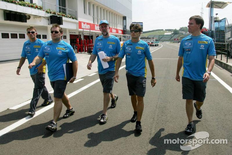 Giancarlo Fisichella detrás de una pista a pie con los miembros del equipo Renault F1