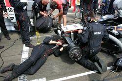 Los miembros del equipo McLaren reparan daños en la parte delantera del coche de Montoya en la parrilla de salida