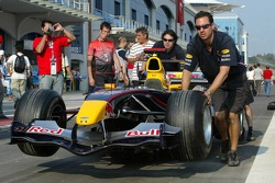 Red Bull Racing team members push car to technical inspection