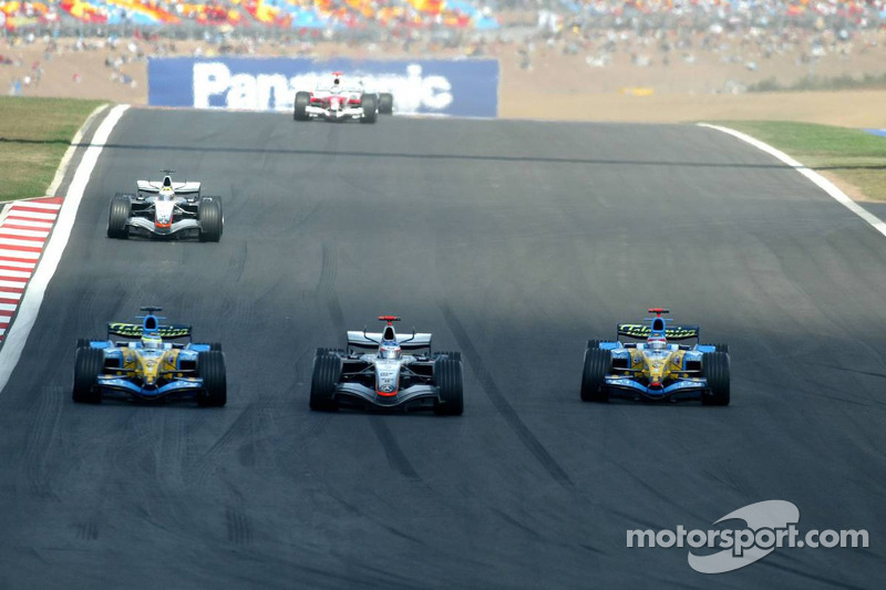 Kimi Raikkonen Giancarlo Fisichella'yı geçerken Fernando Alonso aksiyonu seyrediyor