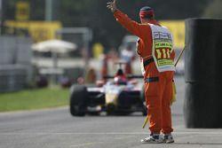 A marshal directs race winner Neel Jani into Parc Fermé