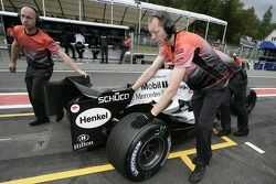 Механики Кими Райкконена толкают его McLaren назад в боксы