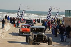 Oude auto's rijden over het strand met toeschouwers