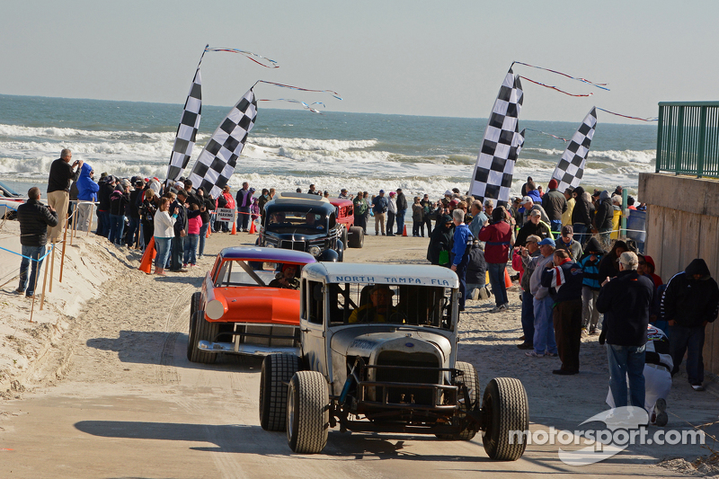Vintage cars complete their run on the beach with crowd looking on.