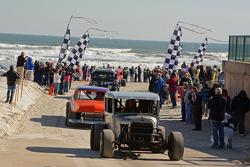 Carros antigos completam corrida na praia com pessoas olhando