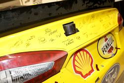 Membros da equipe assinando o carro vencedor