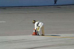 A NASCAR official sets up the pit lane cones