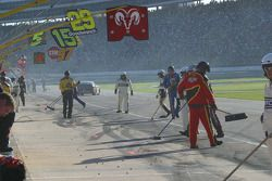 Crews sweep up lug nuts after pit stops