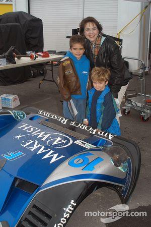 Make-A-Wish escort Lisa Baird with Robert and Adam Duke in Ten Motorsports garage