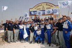 Giniel De Villiers, Tina Thorner, Mark Miller, Dirk von Zitzewitz, Bruno Saby, Michel Périn, Carlos Sainz et Andreas Schulz fêtent la victoire avec les membres de l'équipe Volkswagen Motorsport