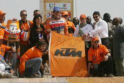 Podium Motos: le vainqueur Marc Coma et les membres de l'équipe KTM rendent hommage à Andy Caldecott