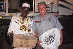 Ronn Bailey distribue des stylos à Mr. Ibrahim pour les enfants de l'école locale