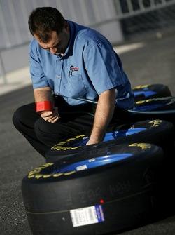 Un membre de l'équipe vérifie la pression des pneus
