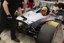 Frank Biela sits in the Audi R10 as engineers work on the nose