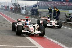 Jenson Button and Rubens Barrichello head to track