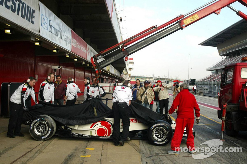 Honda team members put a cover on the Honda Racing RA106