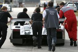 Audi Sport North America team members push the R10 back to the paddock area