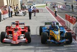 Race winner Fernando Alonso arrives in Parc Fermé with Michael Schumacher