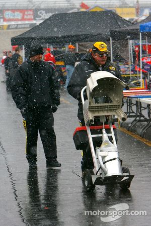 NASCAR official Gene Sanders prepares for technical inspection as snow falls