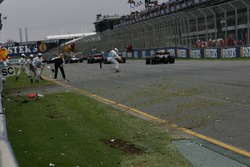 Course marshalls clean up the track after the crash of Michael Schumacher