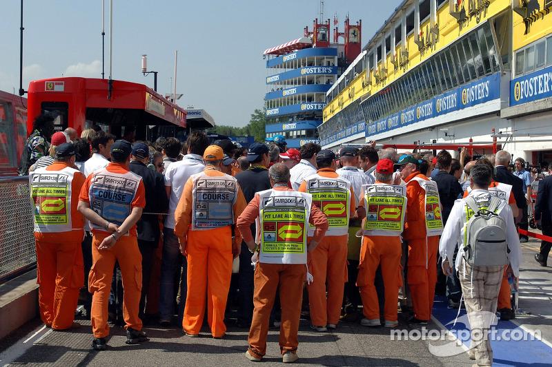 Des mécaniciens et des journalistes dans la voie des stands