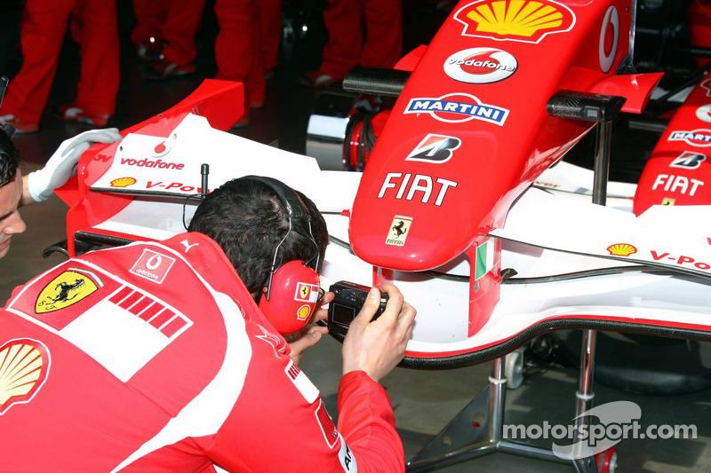 Un mécanicien de Ferrari prend une photo de l'aileron avant