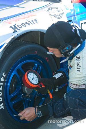 Un équipier de TRG Racing vérifie la pression des pneus