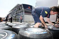 Un membre de l'équipe Red Bull Racing marque des pneus Michelin devant le Energy Station