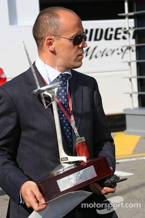 Un homme apporte les trophées des vainqueurs de la Formule 1 dans le paddock