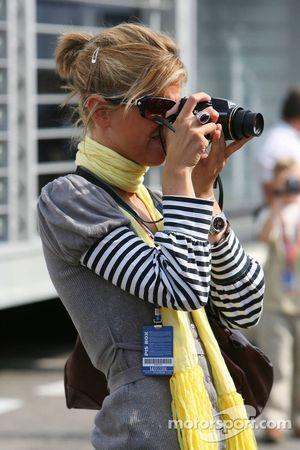 Une jeune femme prend une photo dans le paddock