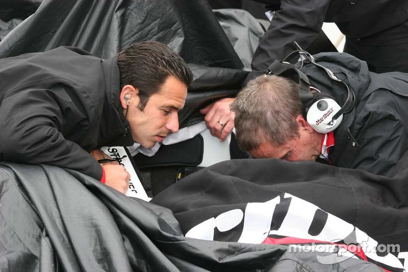 Helio Castroneves aide à travailler sur la voiture pendant la pluie
