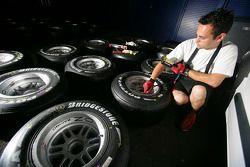 An ART Grand Prix crew member checks tyres