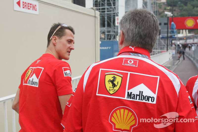 Michael Schumacher y Ross Brawn salen del edificio de los oficiales