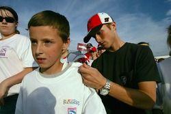 Kasey Kahne signe le t-shirt d'un jeune fan au cours d'une marche de charité de la fondation NASCAR