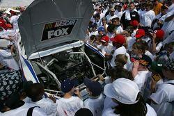 Un groupe de 400 écoliers regardent un moteur d'une voiture NASCAR avant le Neighborhood Excellence 400 présenté par la Banque d'Amérique